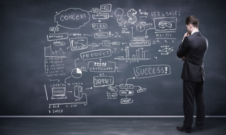 marketing research: man looking at business strategy on blackboard