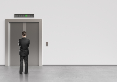 people in elevator: businessman and modern elevator with closed doors