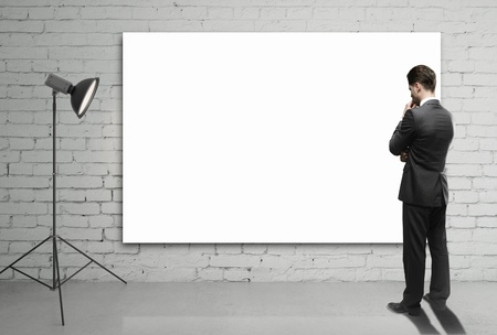 businessman looking at blank poster on wall photo