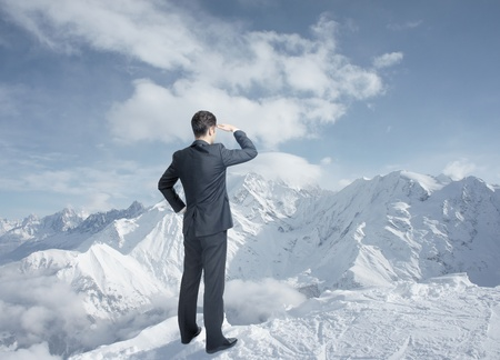 businessman looking to winter mountains photo