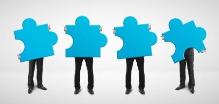 toma de decisiones: cuatro hombre sostiene la tarjeta de rompecabezas azul