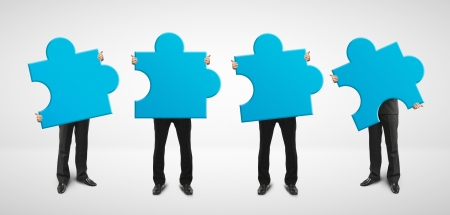 decision making: four man holding blue puzzle card Stock Photo