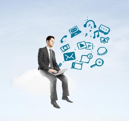 jornada de trabajo: hombre de negocios con ordenador portátil sentado en la nube y las redes sociales ion Foto de archivo