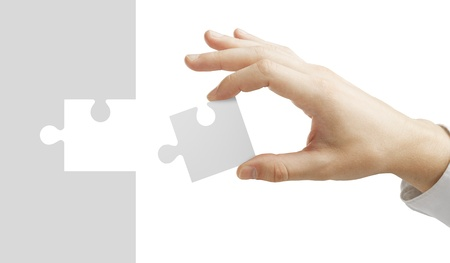 implementation: hand puts puzzle isolated on white