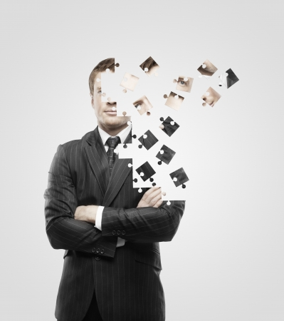 liderazgo: hombre de negocios construido de rompecabezas en el fondo blanco Foto de archivo