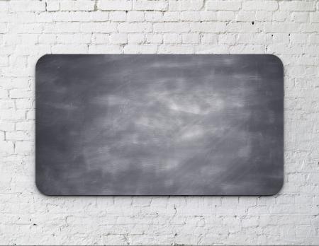 message board: Black blackbord on brick wall