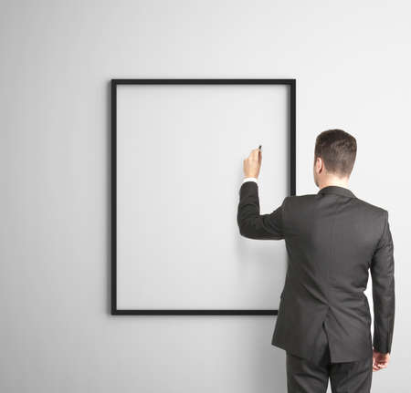 black businessman: businessman drawing on black frames on wall