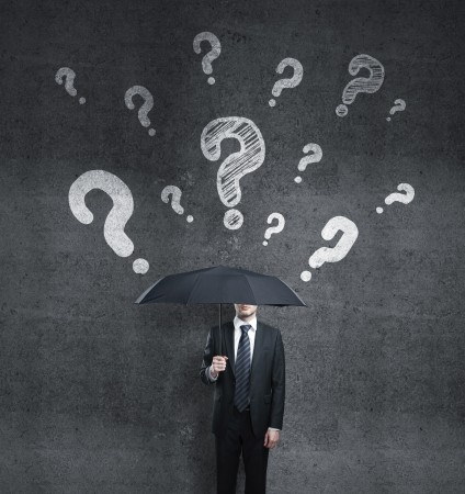 businessman with umbrella and question mark photo
