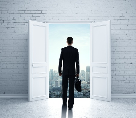 businessman walking in open door to city photo