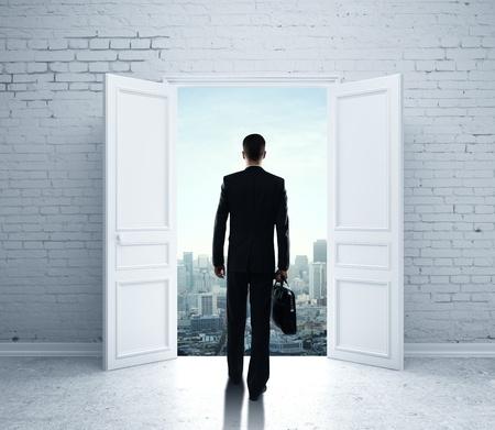 room door: businessman walking in open door to city