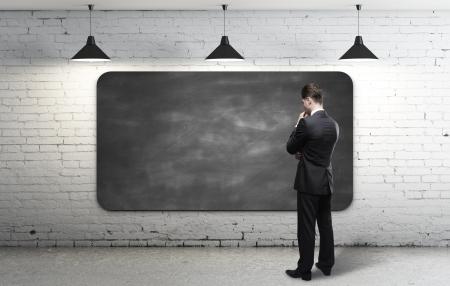 dirty room: businessman looking at blackboard in loft interior
