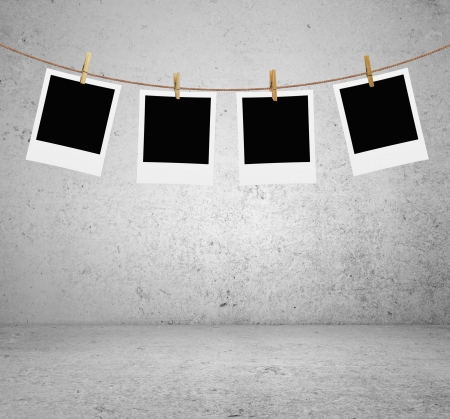 recollection: photos hanging on a rope in brick room Stock Photo