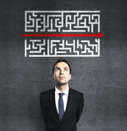 banker: businessman looking at maze with red arrow
