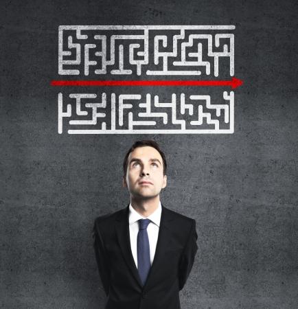 the maze: hombre de negocios mirando laberinto con la flecha roja