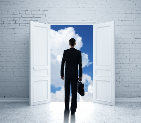 man with briefcase open door to blue sky photo