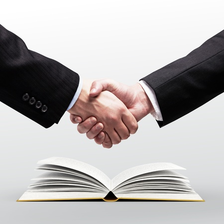 handshake and open book on white background Stock Photo - 18505104