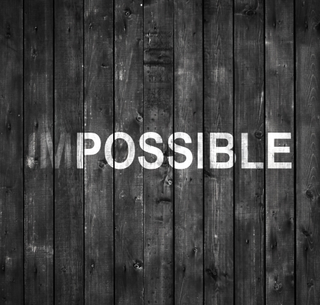 impossible text on gray wooden wall Stock Photo