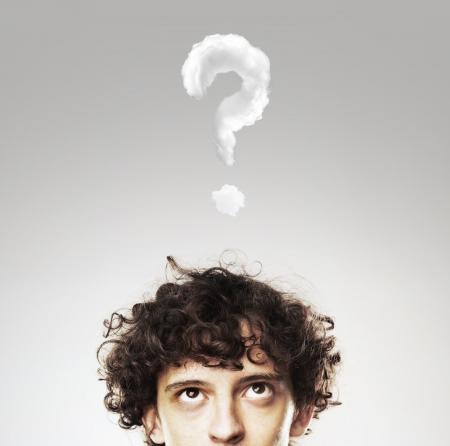 hombres jovenes: hombres que piensan con signo de interrogación sobre fondo blanco Foto de archivo