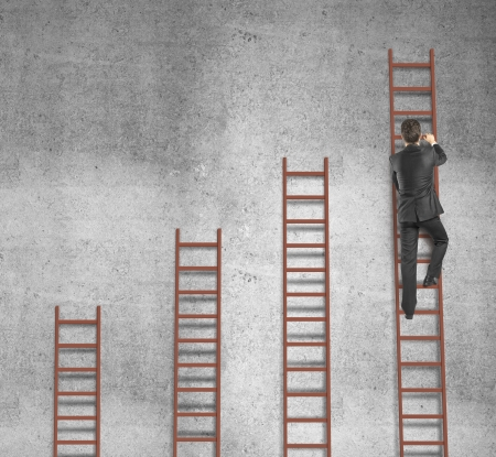 climbing ladder: man climbing on ladder and concrete wall Stock Photo