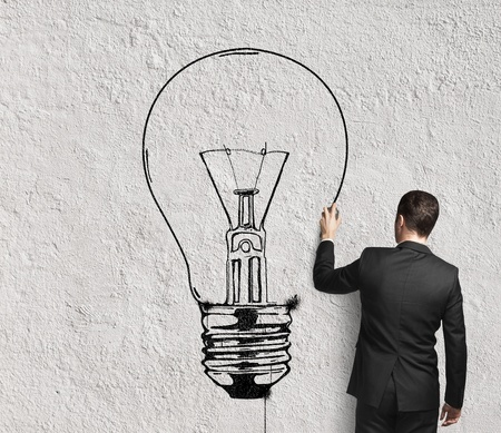 business goal: businessman drawing lamp on wall