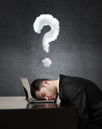 businessman sleep on laptop and question mark photo