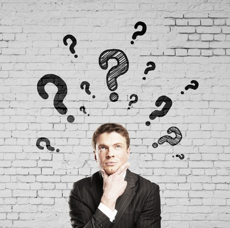 businessman thinking with question mark and brick wall photo