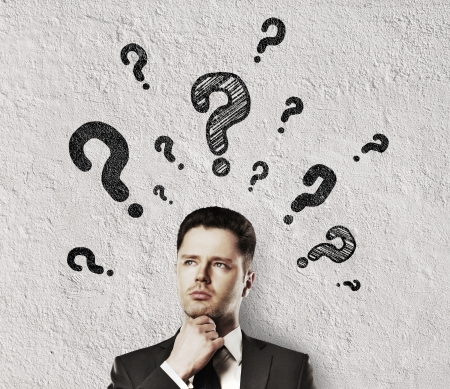 man thinking with question mark and concrete wall photo