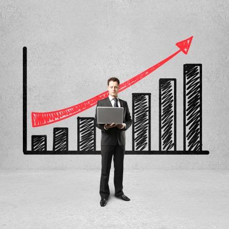 businessman holding laptop near of chart profits photo