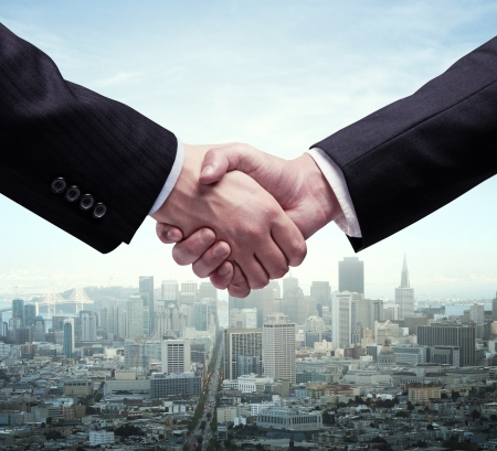 cooperation: handshake and modern city on background Stock Photo
