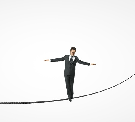businessman walking on rope on a white background photo