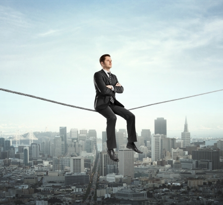 confident man: businessman sitting on rope and city
