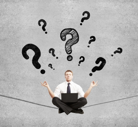businessman sitting on rope and question mark photo