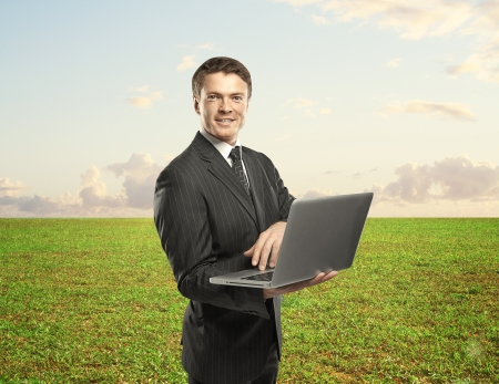 man with notebook standing on green field photo