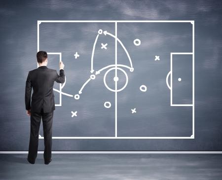 schemes: man drawing tactic scheme on big black desk board Stock Photo