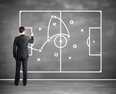 tactic: businessman drawing tactic scheme on big black desk board