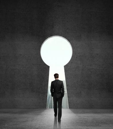 mannen lopen naar geopend betonnen muur in de vorm van een sleutelgat Stockfoto