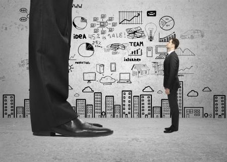 little business man: pie grande y peque�o hombre de negocios y la estrategia en la pared
