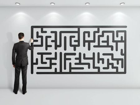 businessman drawing maze on white wall photo