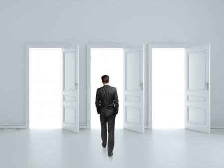 businessman walking to opened three door photo