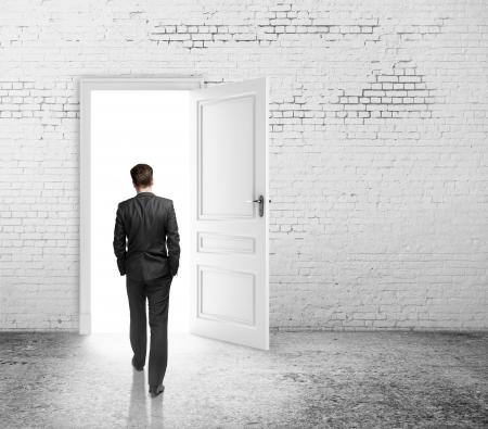 abriendo puerta: empresario caminando a puerta altillo abierto Foto de archivo