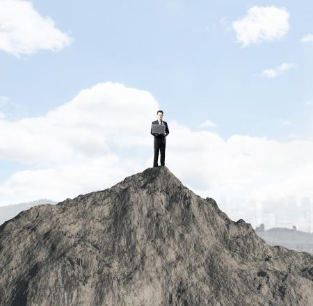 mountin: businessman with laptop standing onmountin