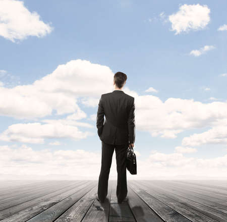 businessman standng on wooden floor and looking  blue sky photo