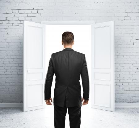 businessman standing and looking open door photo