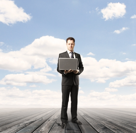 laptop stand: businessman with laptop on wood floor and blue sky background