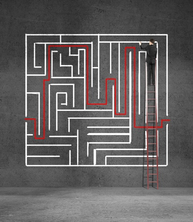 man climbing on ladder drawing maze photo