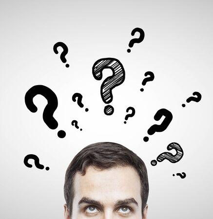 灰色の背景で質問記号を持つ男