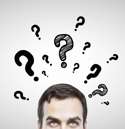 questions: man with questions symbol on gray background