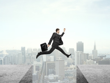 businessman jumping from roof to roof on city