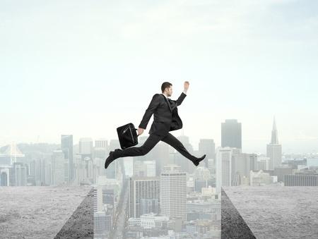 springende mensen: zakenman springen van dak naar dak op de stad