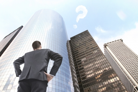 man standing and looking on skyscraper